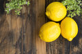 Three lemons and mint on a rustic wooden background Stock Photos