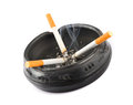 Three Lit Cigarettes in a Black Ashtray Royalty Free Stock Photo