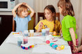 Three little girls painting on Easter eggs Stock Photo