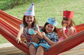 Three little girls wearing paper crowns and eating ice cream having fun in orange hamac Stock Image