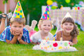 Three little kids celebrating birthday on green grass Royalty Free Stock Photography