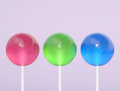 Three lollipops on a purple background Royalty Free Stock Photo