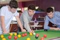 Three men around pool table Royalty Free Stock Photo
