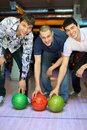 Three men bent over to heave up balls for bowling Stock Image