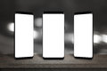 Three mobile phones with screen for mockup on the table Royalty Free Stock Photo