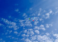 Three multi colored balloons fly in the blue sky with clouds hover Stock Photo