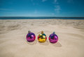 Three multi-colored, bright Christmas balls lie on the sand by the ocean, the sea. Royalty Free Stock Photo
