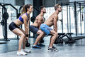 Three muscular athletes squatting together side view of with kettlebells Stock Images