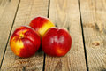 Three nectarines closeup of on wood planks Stock Photo