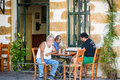Three old men sitting at greek taverna and playing backgammon Royalty Free Stock Photo