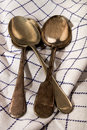 Three old silver spoons on a blue and white kitchen towel Royalty Free Stock Photo