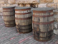 Three old wooden barrels and weathered covered sitting by a stone wall in a brick alley Stock Images
