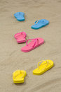 Three pairs of colorful flip flops on white sand beach Royalty Free Stock Image