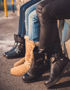 Three pairs of girls legs with boots on them sitting a wall Stock Images