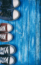 Three pairs of old sneakers on blue worn wooden background Royalty Free Stock Photo