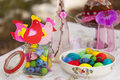 Three paper figurines of chickens sitting on glass jar with colorful beads and round of plate with several colorful easter eggs Royalty Free Stock Photo