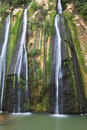 Three parallel streams of water unusual jet waterfall running down the steep slope and fall in oval pool Royalty Free Stock Photo