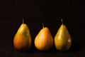 Three pears on black golden background standing upright Royalty Free Stock Photography