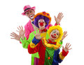 Three people dressed up as colorful funny clowns over white background Royalty Free Stock Images