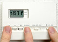 Three persons adjust thermostat digital Stock Image