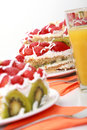 Three pieces of homemade cake is served with orange juice fruit strawberries and kiwi on the table Royalty Free Stock Photos