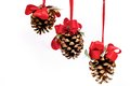 Three pine cones hanging from red ribbons on isolated white background Stock Photography