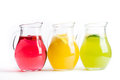 Three pitchers with red yellow green fruit juice on a white ba cool bright colors Royalty Free Stock Photo