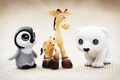 Three plastic toy figurines penguin giraffe and white teddy bear Royalty Free Stock Photos