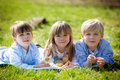 Three preschool kids, siblings, playing in the park with little Royalty Free Stock Photo