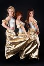 Three pretty girls dancing trio of young beautiful women in costumes over black background Royalty Free Stock Photo