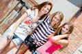 Three pretty teenage young women girl friends with different hair smiling happy looking at camera Royalty Free Stock Photography