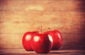Three red apples on wooden table photo in retro color style Royalty Free Stock Images