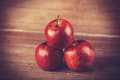 Three red apples on wooden table photo in retro color style Royalty Free Stock Photo