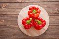 Three red bell peppers on cutting board on a wooden background Royalty Free Stock Photo