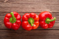 Three red bell peppers on a wooden background. Top view Royalty Free Stock Photo