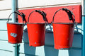 Three red buckets hanging on pegs Royalty Free Stock Photos