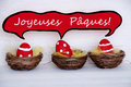 Three red easter eggs with comic speech balloon french joyeuses paques means happy easter dotted and striped in baskets or nest on Royalty Free Stock Images