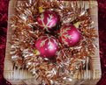 Three Red and Gold Christmas Baubles on Gold Tinsel in Wicker Box Royalty Free Stock Photo