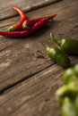 Three red hot chili peppers with green peppers Royalty Free Stock Photo