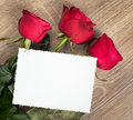 Three red roses and blank sheet on wood wooden Stock Photo