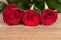 Three red roses wood background Royalty Free Stock Images