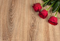 Three red roses wood background Royalty Free Stock Photo