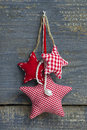 Three red white checkered handmade christmas stars hanging on a