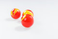 Three red yellow marbles  on white Royalty Free Stock Photo
