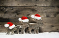Three reindeer wearing santa hats on brown wooden background. Royalty Free Stock Photo