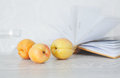 Three ripe apricots on background of open pages of book Royalty Free Stock Photo