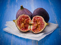 Three ripe figs on blue background Royalty Free Stock Photo