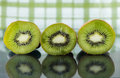 Three ripe kiwi slices sitting on a reflective surface horizontal image of of placed for reflection and green and white checkered Royalty Free Stock Images