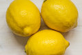 Three ripe lemons on the table top view Royalty Free Stock Image