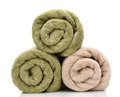 Three rolled bath towels freshly laundered on a white background with reflection closeup looking at the towel ends Royalty Free Stock Photos